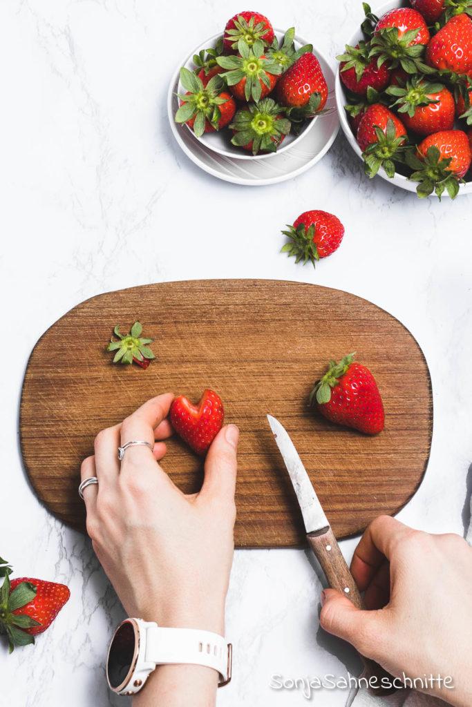 Erdbeer-Herzen: Erdbeeren in Herzform schneiden ist super einfach, schnell gemacht ins unglaublich dekorativ. Egal ob ihr Kuchen, Torten, Desserts oder euer Müsli dekorieren wollt. Die Herzen werdet ihr bestimmt nicht nur zum Muttertag oder am Valentinstag machen. Probiert die 3 Schritte Anleitung doch gleich mal aus. #erdbeeren #deko #süßeSachen #selbermachen #SonjaSahneschnitte